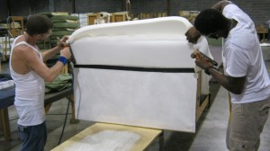 Erin and Teko upholster the foam on a Jennings loveseat.